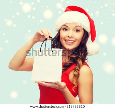 shopping, sale, gifts, christmas, x-mas concept - smiling woman in red dress and santa helper hat with shopping bag - stock photo