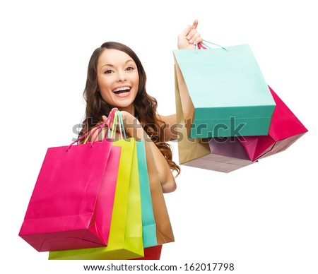 shopping, sale, gifts, christmas, x-mas concept - smiling woman in red dress with colorful shopping bags - stock photo
