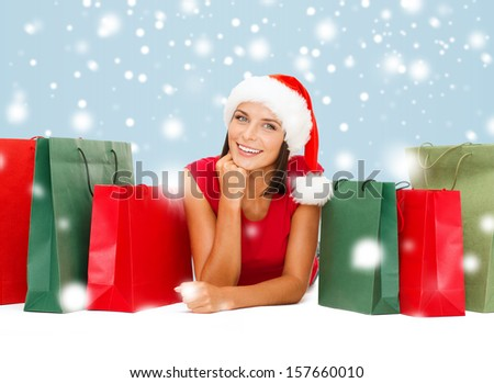 shopping, sale, gifts, christmas, x-mas concept - smiling woman in red shirt and santa helper hat with shopping bags - stock photo