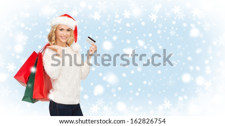 shopping, sale, gifts, christmas, x-mas concept - smiling woman in santa helper hat with shopping bags and credit card - stock photo
