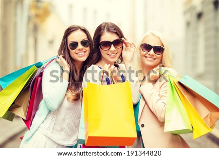 shopping, sale, happy people and tourism concept - three beautiful girls in sunglasses with shopping bags in ctiy - stock photo