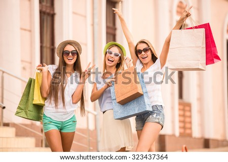 shopping, sale, happy people and tourism concept - three beautiful girls in sunglasses with shopping bags in city