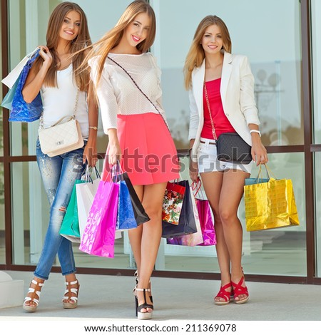 shopping, sale, happy people and tourism concept - three beautiful girls  with shopping bags in ctiy
