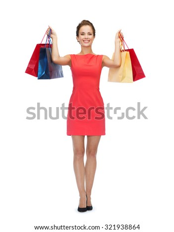 shopping, sale, people, gifts and holidays concept - smiling woman in red dress with shopping bags - stock photo