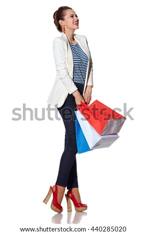 Shopping. The French way. Full length portrait of excited young woman with French flag colours shopping bags on white background looking aside