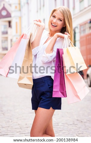 Shopping therapy. Beautiful young cheerful woman holding shopping bags and looking at camera while standing outdoors