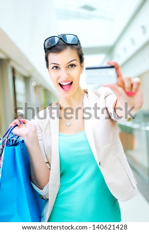 Shopping time, attractive woman at mall holding bags and credit card, focus on credit card - stock photo