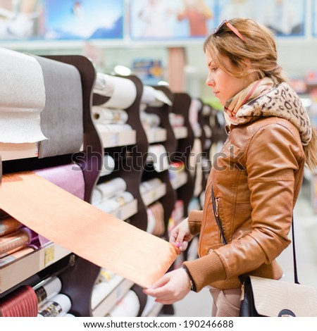 shopping time: beautiful blond young woman having fun in the DIY supermarket department store choosing for buying wallpaper holding & looking at design image - stock photo