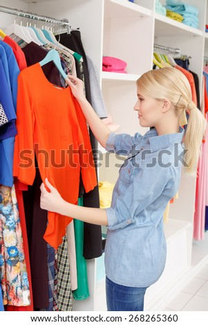 Shopping time. Joyful female shopper holding a hanger with a red blouse at clothing shop - stock photo