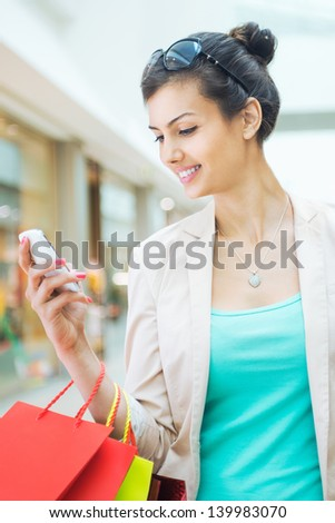 Shopping time, woman at mall with smart phone - stock photo