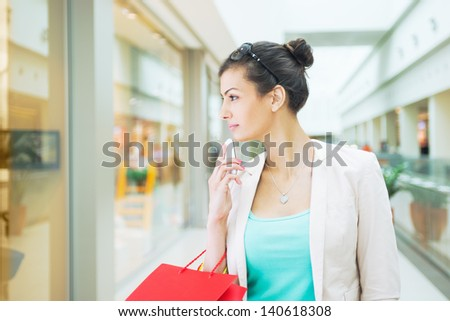 Shopping time, woman at mall with smartphone, looking at windows, shallow dof - stock photo