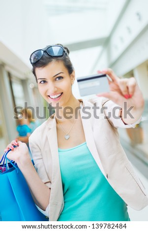 Shopping time, woman at shopping mall showing credit card - stock photo