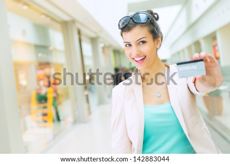 Shopping time Young woman at mall, showing credit card, focus on face - stock photo