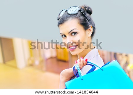 Shopping time, young woman at mall with shopping bags - stock photo