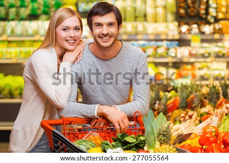 Shopping together for dinner. Cheerful young couple smiling at camera and standing behind their shopping cart in a food store - stock photo
