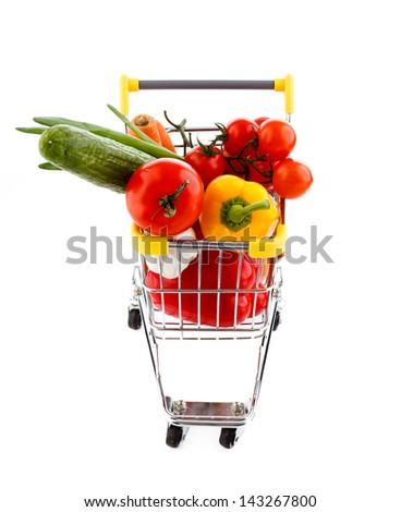 Shopping trolley full of goods on white background - stock photo