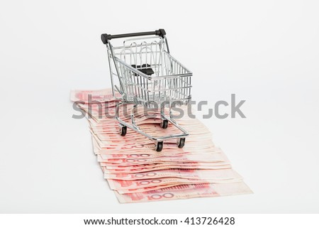 Shopping trolley full of Yuan - currency. Symbolic example of spending money in shops, or advantageous purchase in the shopping center. Yuan notes from China's currency. Chinese banknotes - stock photo