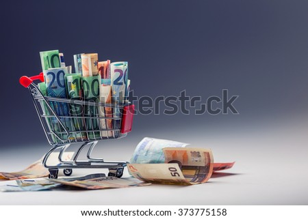 Shopping trolley. Shopping cart. Shopping trolley full of euro money - banknotes - currency. Symbolic example of spending money in shops, or advantageous purchase in the shopping center. - stock photo