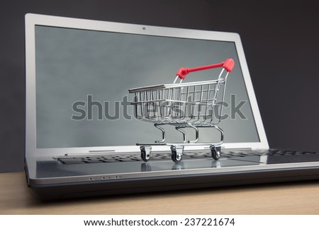 Shopping trolley sitting on open laptop - stock photo