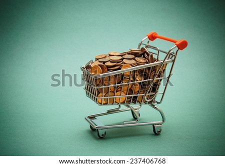 Shopping trolley with coins on a green background - stock photo