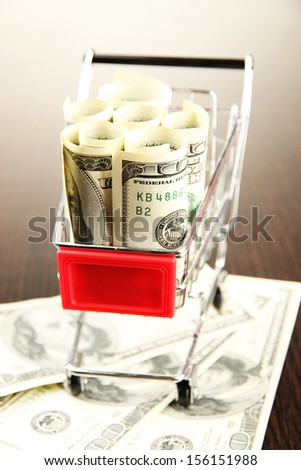 Shopping trolley with dollars, on dark background - stock photo