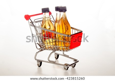 shopping trolley with filled apple juice bottles on bright background - stock photo