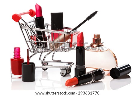 Shopping trolley with make-up products over white background - stock photo