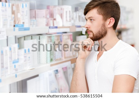 Shopping wisely. Closeup portrait of a handsome young bearded man choosing products from an aisle at the store copyspace