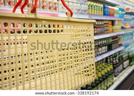 Shopping with cream plastic basket. Browsing the available goods in hypermarket. - stock photo