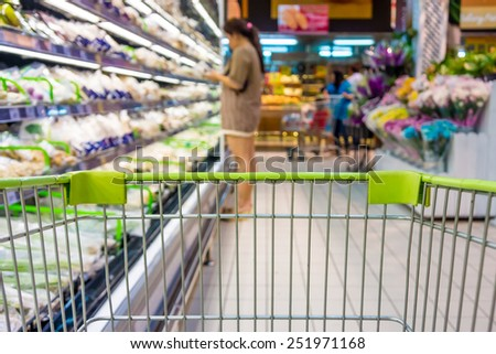 Shopping with shopping cart in vegetable department of supermarket - stock photo