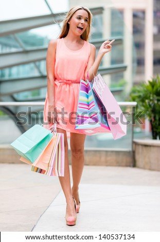 Shopping woman at the mall holding bags - stock photo