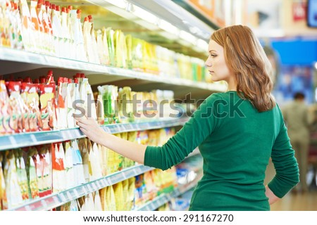 Shopping. Woman choosing bio food cheese products in dairy store or supermarket - stock photo