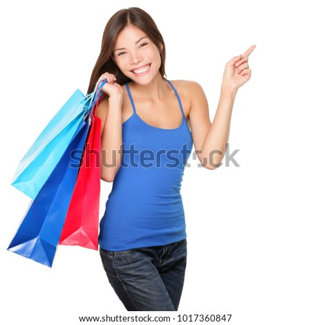 Shopping woman excited about new purchases or sale holding blue and red shopping bags pointing to the side copy space. Happy multiracial model in studio cutout portrait isolated on white background.