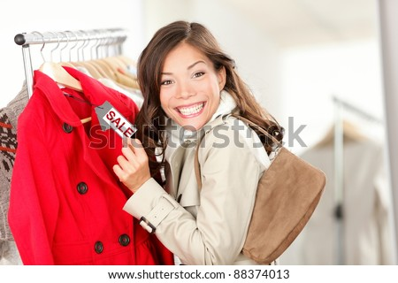 Shopping woman excited showing price tag at clothes sale in clothing store. Smiling cheerful woman. Price label reads sale. - stock photo