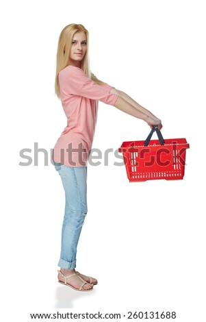 Shopping woman. Full length of surprised casual young woman standing smiling with empty shopping cart basket looking out of frame, over white background