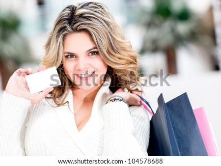 Shopping woman holding a white contact card and smiling - stock photo