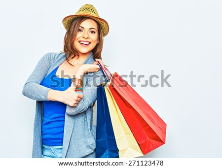 Shopping woman holding bags show thumb up. One smiling girl portrait on white studio wall background. Yellow hat. - stock photo