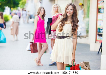 Shopping woman holding bags with a group of friends at the background - stock photo