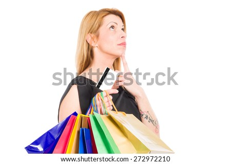 Shopping woman holding credit or debit card and thinking