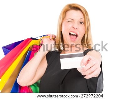 Shopping woman holding credit or debit card and wink to the camera - stock photo
