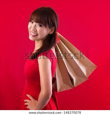 Shopping woman holding shopping bags looking at camera on red background. Beautiful young Asian shopper smiling happy. - stock photo