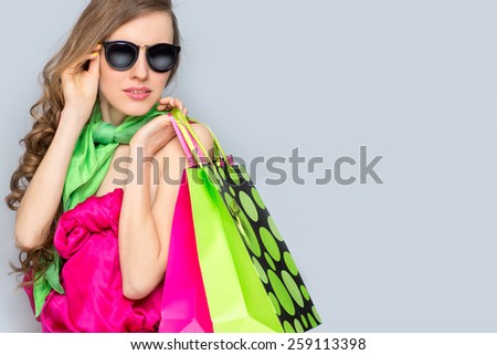 Shopping woman holding shopping bags looking  to the side on grey background wearing bright clothing - stock photo