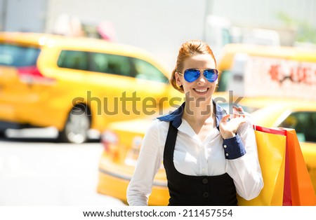 Shopping woman in New York City. Beautiful happy, smiling summer shopper holding shopping bags walking outside with yellow taxi cab in background. Positive emotions. Caucasian model in Manhattan, USA. - stock photo