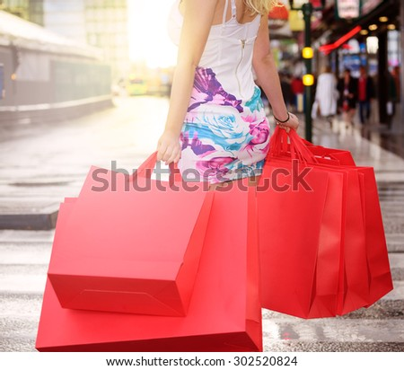 Shopping woman in sunset after rain
