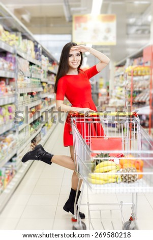 Shopping Woman Looking at the Shelves in the Supermarket - Portrait of a young girl in a market store with a shopping cart  - stock photo