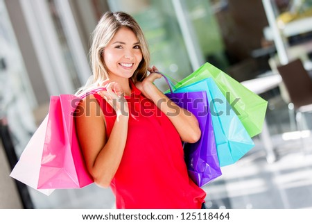 Shopping woman looking very happy at the mall - stock photo