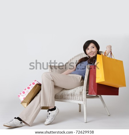 Shopping woman of Asian sit on chair and holding bags with smiling.