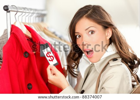 shopping woman shocked and surprised over price looking at price tag on coat or jacket. Woman shopper shopping for clothes inside in clothing store. Funny image of Asian / Caucasian female model.