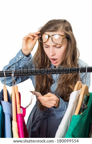 Shopping woman shocked over price tag. Funny shopper woman staring amazed at price - stock photo