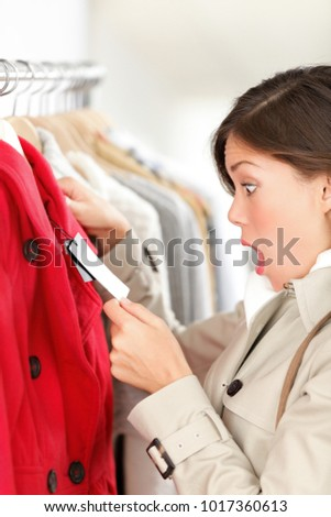 Shopping woman shocked surprised over price looking at price tag on winter coat or spring jacket. Woman shopper shopping for clothes in clothing store. Funny Asian girl.